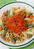Colored pasta with tomato sauce. On plate Royalty Free Stock Images