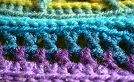 Colored pattern crochet fabric background. Crocheted yarn making a textured pattern Stock Photos