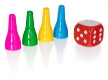Colored pawns and red dice. Set pieces in the colors yellow, green, blue. Cube in red with white eyes. Stock Photo