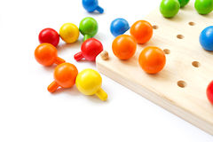 Colored pegs board, wood beads on white background. Pegs, colorful, tree, game, isolate Stock Image