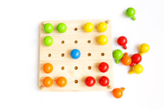 Colored pegs board, wood beads on white background. Pegs, colorful, tree, game, isolate Stock Photography
