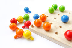 Colored pegs board, wood beads on white background. Pegs, colorful, tree, game, isolate Royalty Free Stock Photography