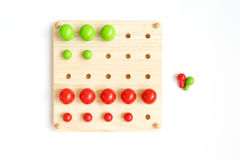 Colored pegs board, wood beads on white background. Pegs, colorful, tree, game, isolate,math Stock Photo