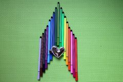 Colored pen arranged in the shape of the arrow, above there is a love silver hairpin, flat on a green background, children`s favor Royalty Free Stock Photography