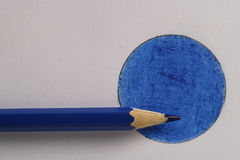 Colored pencil on blue disk. Colored pencil on a blue circle drawn in pencil Stock Image