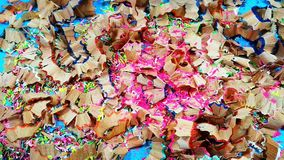 Colored pencil core wax falling on wooden chips. Pink colored pencil being sharpened and core wax remains falling on bundle of wooden chips from other pencils stock video footage