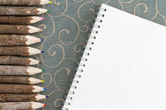 Colored pencil crayons and a blank notebook Royalty Free Stock Images
