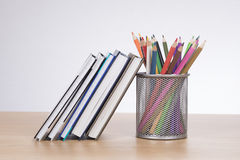 Colored pencil crayons with textbooks for school. Colored pencil crayons in a mesh container with textbooks and journals for school standing together on a wooden Stock Images
