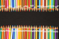 Colored Pencil Ends. Colored Pencils in a row on top and bottom of image with a black background royalty free stock images