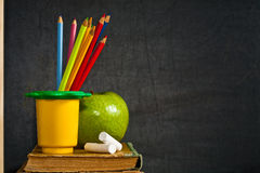 Colored pencil and green apple on old textbook. Colored pencil, chalk and green apple on old textbook against blackboard in classroom Royalty Free Stock Photography