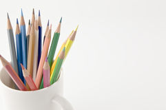 A colored pencil is put in a coffee cup. Stock Photography