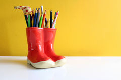 Colored Pencil in Red Boot. Several Colored Pencil in Red Boot with Yellow Background Stock Images