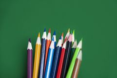 Colored pencil set on green background back to school and education concept / Crayons colorful stock images