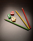 Colored Pencil Sharpeners and Pencils. Various colored pencils and pencil sharpeners on plain surface Royalty Free Stock Images