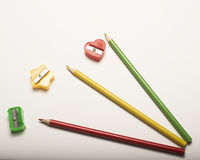 Colored Pencil Sharpeners and Pencils. Various colored pencils and pencil sharpeners on plain surface Stock Photo
