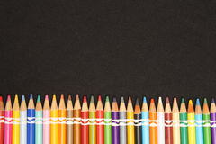 Colored Pencil Tips - Image 3. Colored Pencils in a row on bottom of image with a black background stock photo