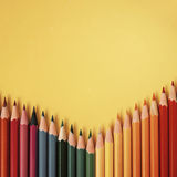 Colored pencil on yellow paper background for drawing color circle Stock Image