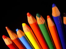 Colored Pencils. A line of brightly colored pencils against a black background Royalty Free Stock Photos
