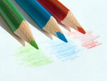 Colored pencils. Three colored pencils on white paper sheet Royalty Free Stock Photography