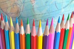 Colored pencils. Set on background of the globe Stock Images