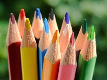 Colored pencils. Close-up of some colored pencils over a green background Royalty Free Stock Images