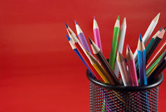 Colored pencils. Colored pencils in a black mesh holder on the red background Stock Photography