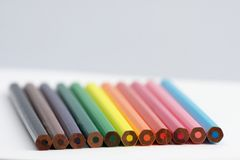 Colored pencils. Aligned on a white drawing paper Royalty Free Stock Photography