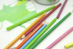 Colored pencils and abstract paints on white background royalty free stock photography