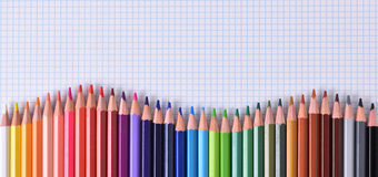 Colored pencils aligned waveform palette on checkered sheet. Of paper. Top view Stock Photography