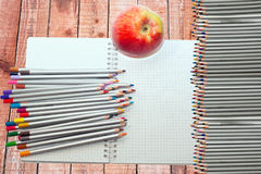 Colored pencils, aple and notebook Royalty Free Stock Photography