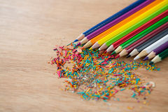 Colored pencils arranged in diagonal line with pencil shavings Royalty Free Stock Photos