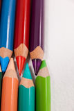 Colored pencils arranged in interlock pattern on white background Stock Images