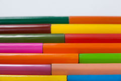 Colored pencils arranged in interlock pattern on white background Stock Photo