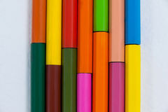 Colored pencils arranged in interlock pattern on white background Royalty Free Stock Photography
