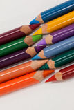 Colored pencils arranged in interlock pattern on white background Royalty Free Stock Photo