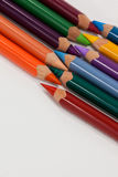 Colored pencils arranged in interlock pattern on white background Stock Photos