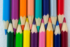 Colored pencils arranged in interlock pattern on white background Royalty Free Stock Image
