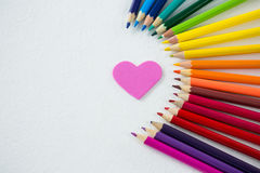 Colored pencils arranged in semi circle with heart on white background Stock Images