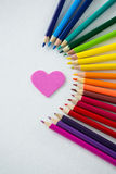 Colored pencils arranged in semi circle with heart on white background Royalty Free Stock Photo