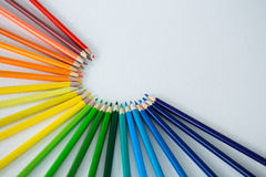 Colored pencils arranged in semi circle on white background Royalty Free Stock Photography