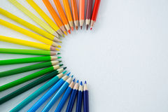 Colored pencils arranged in semi circle on white background Stock Image