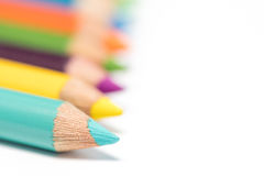 Colored pencils in an arrangement on a white background Royalty Free Stock Photos