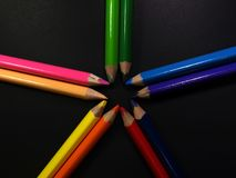 Star array. Colored pencils array in a dark paper background royalty free stock photo
