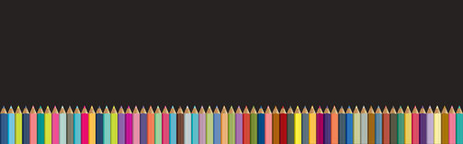 Colored pencils background. Black board with  crayons. Royalty Free Stock Images