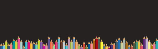 Colored pencils background. Black board with  crayons. Stock Image