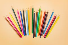 Colored pencils on a beige background stock photo