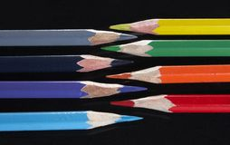 Colored pencils on black. Set of colored pencils on black stock images