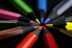 Colored pencils on black background royalty free stock photos