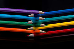 Colored pencils on black background reflected in water. Stock Photo