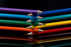 Colored pencils on black background reflected in water. Royalty Free Stock Images